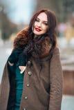 Muchacha hermosa en un vestido y una capa con un cuello de la piel Maquillaje brillante elegante, labios rojos, mirando la cámara Fotografía de archivo