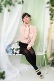 Mujer que se sienta en el oscilación en el verde Foto de archivo