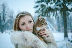 Muchacha hermosa en una capa corta beige con el pelo que fluye que sostiene un gato imagenes de archivo