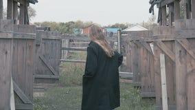 Muchacha hermosa en una capa negra contra la perspectiva de la cerca del pueblo almacen de metraje de vídeo