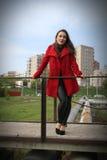 Muchacha hermosa en una capa roja que se aferra a la verja en el puente Fotos de archivo