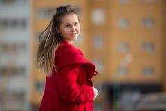 Muchacha hermosa en una capa roja y vidrios en el fondo de la casa Fotos de archivo libres de regalías