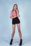 Muchacha hermosa en una colocación de la camisa y de los pantalones cortos Foto de archivo
