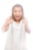 Muchacha hermosa en una hoja blanca detrás de un vidrio mojado Fotos de archivo