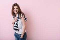 Muchacha hermosa en una pared rosada del fondo Fotografía de archivo
