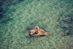 Muchacha hermosa en una roca en el medio del mar con el paraguas Imagen de archivo