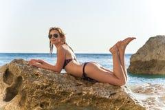 Muchacha hermosa en una roca en una playa imagen de archivo