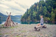 Muchacha hermosa en una sudadera con capucha Verde azul del lago mountain El fuego Imagen de archivo libre de regalías