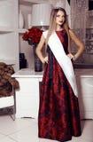 Muchacha hermosa en vestido, corona y cinta rojos elegantes del título Fotos de archivo libres de regalías