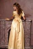Muchacha hermosa en vestido de oro foto de archivo