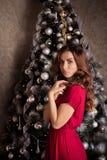 Muchacha hermosa en vestido rojo en el árbol de navidad Imágenes de archivo libres de regalías