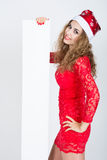Muchacha hermosa en vestido rojo en un sombrero de la Navidad que sostiene banderas Foto de archivo