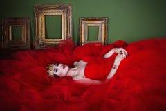 Muchacha hermosa en vestido rojo largo y en corona real Fotografía de archivo
