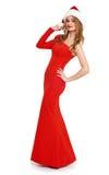 Muchacha hermosa en vestido rojo y el sombrero de santa aislados en el fondo blanco, concepto del día de fiesta de la Navidad Foto de archivo