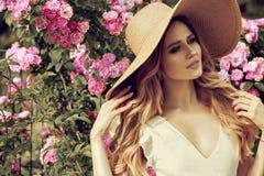 Muchacha hermosa en vestido rosado del vintage y el sombrero de paja que se colocan cerca de las flores coloridas Trabajo de arte fotos de archivo