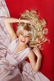 Muchacha hermosa en vestido rosado en fondo rojo Imagen de archivo libre de regalías