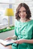 Muchacha hermosa en vestido verde con la tableta Fotografía de archivo libre de regalías