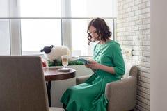 Muchacha hermosa en vestido verde con la tableta Imagen de archivo libre de regalías
