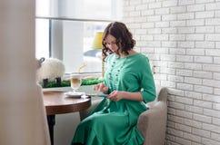 Muchacha hermosa en vestido verde con la tableta Foto de archivo libre de regalías