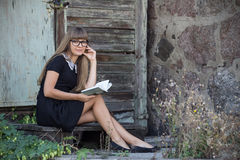 Muchacha hermosa en vidrios negros que lee un libro Fotografía de archivo