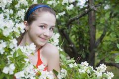 Muchacha hermosa entre las flores Imágenes de archivo libres de regalías