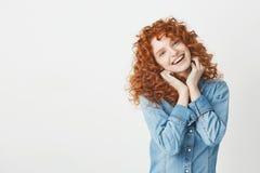 Muchacha hermosa feliz con el pelo rojo rizado que sonríe mirando la cámara sobre el fondo blanco Copie el espacio Imágenes de archivo libres de regalías