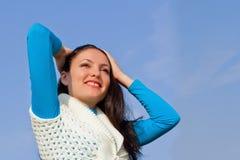 Muchacha hermosa feliz contra el cielo azul Foto de archivo libre de regalías