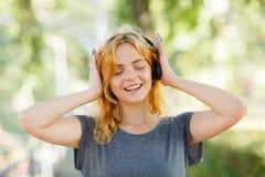 Muchacha hermosa feliz del estudiante que sonríe en auriculares en un fondo del parque Concepto del amante de la música Imagenes de archivo