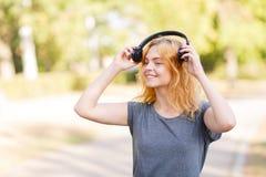 Muchacha hermosa feliz del estudiante que sonríe en auriculares en un fondo del parque Concepto del amante de la música Fotografía de archivo libre de regalías