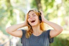 Muchacha hermosa feliz del estudiante que sonríe en auriculares en un fondo del parque Concepto del amante de la música Foto de archivo libre de regalías