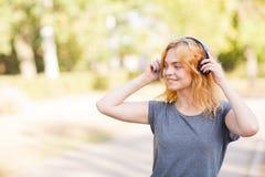 Muchacha hermosa feliz del estudiante que sonríe en auriculares en un fondo del parque Concepto del amante de la música Fotografía de archivo