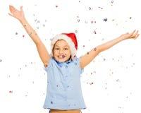 Muchacha hermosa feliz en confeti del tiro del casquillo de Papá Noel Fotografía de archivo libre de regalías