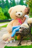 muchacha hermosa feliz en un banco con un oso de peluche Foto de archivo libre de regalías