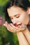 Muchacha hermosa feliz que come las frambuesas, sosteniendo bayas en la palma de su mano Imagen de archivo