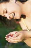 Muchacha hermosa feliz que come las frambuesas, sosteniendo bayas en la palma de su mano Foto de archivo libre de regalías