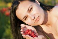 Muchacha hermosa feliz que come las frambuesas, sosteniendo bayas en la palma de su mano Fotografía de archivo libre de regalías