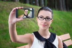Muchacha hermosa feliz que hace la foto del selfie en el teléfono móvil Imágenes de archivo libres de regalías