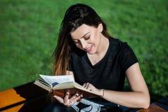Muchacha hermosa feliz que lee un libro en día de primavera soleado en un banco en naturaleza Imágenes de archivo libres de regalías