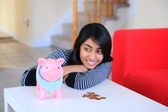 Muchacha hermosa india que mira a su piggybank Foto de archivo libre de regalías