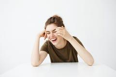 Muchacha hermosa joven alegre feliz con sentarse de risa sonriente del bollo en la tabla sobre el fondo blanco Foto de archivo