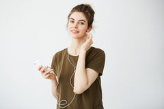 Muchacha hermosa joven con el bollo que sonríe mirando música que escucha de la cámara en auriculares sobre el fondo blanco Imágenes de archivo libres de regalías
