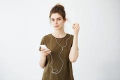 Muchacha hermosa joven con el bollo que sonríe mirando música que escucha de la cámara en auriculares sobre el fondo blanco Imagen de archivo