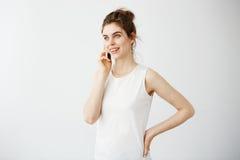 Muchacha hermosa joven con el discurso sonriente del bollo en el teléfono sobre el fondo blanco Fotos de archivo