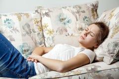 Muchacha hermosa joven con el dolor de estómago que miente en el sofá Foto de archivo libre de regalías
