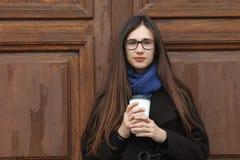 Muchacha hermosa joven con el pelo extralargo magnífico en una capa negra y una bufanda azul con la taza de café disponible que s Foto de archivo libre de regalías