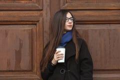 Muchacha hermosa joven con el pelo extralargo magnífico en una capa negra y una bufanda azul con la taza de café disponible que s Fotos de archivo libres de regalías