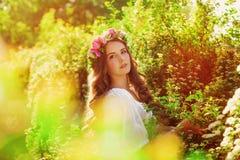 Muchacha hermosa joven con el pelo largo en guirnalda floral en la primavera Imagenes de archivo