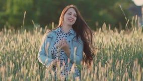 Muchacha hermosa joven con el pelo largo oscuro entre las espiguillas verdes en un campo de trigo que disfruta de la naturaleza y almacen de metraje de vídeo