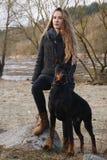 Muchacha hermosa joven con el perro del doberman Fotografía de archivo libre de regalías