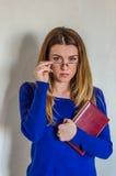 Muchacha hermosa joven con el profesor largo del pelo con los vidrios con un libro en sus manos después de la conferencia Fotos de archivo